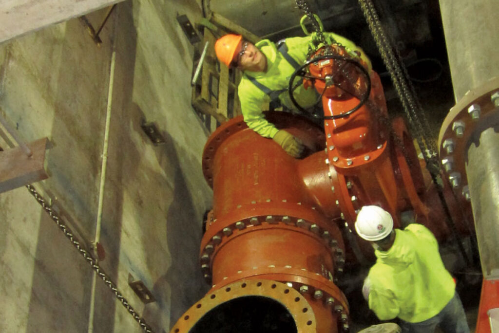 2 workers installing pipes in pit