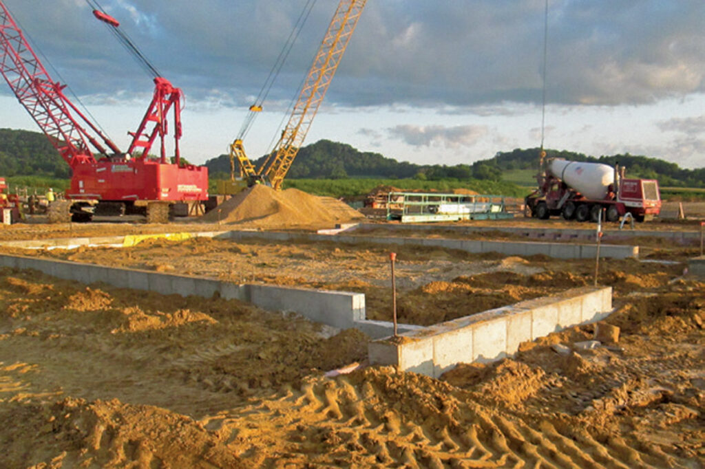 construction site with trucks and cranes