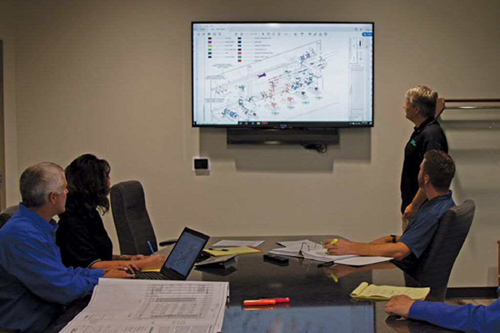 staabco employees looking at a 3d model on a screen