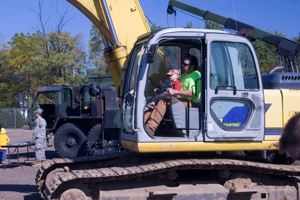 a Staab employee sitting in an excavator with a little boy
