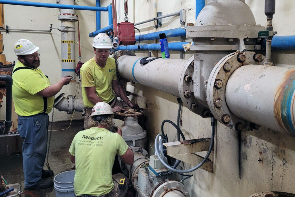 Staab employees working on a mechanical system