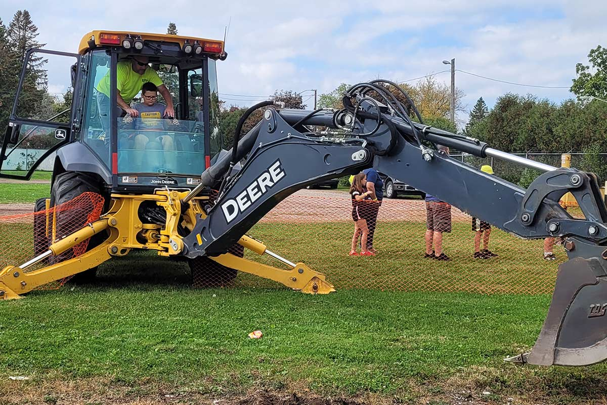 Staab employee showing a kid how to use an excavator